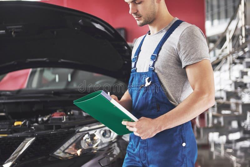Concetto di servizio, di riparazione, di manutenzione e della gente dell'automobile - uomo o fabbro del meccanico con la lavagna  fotografie stock libere da diritti