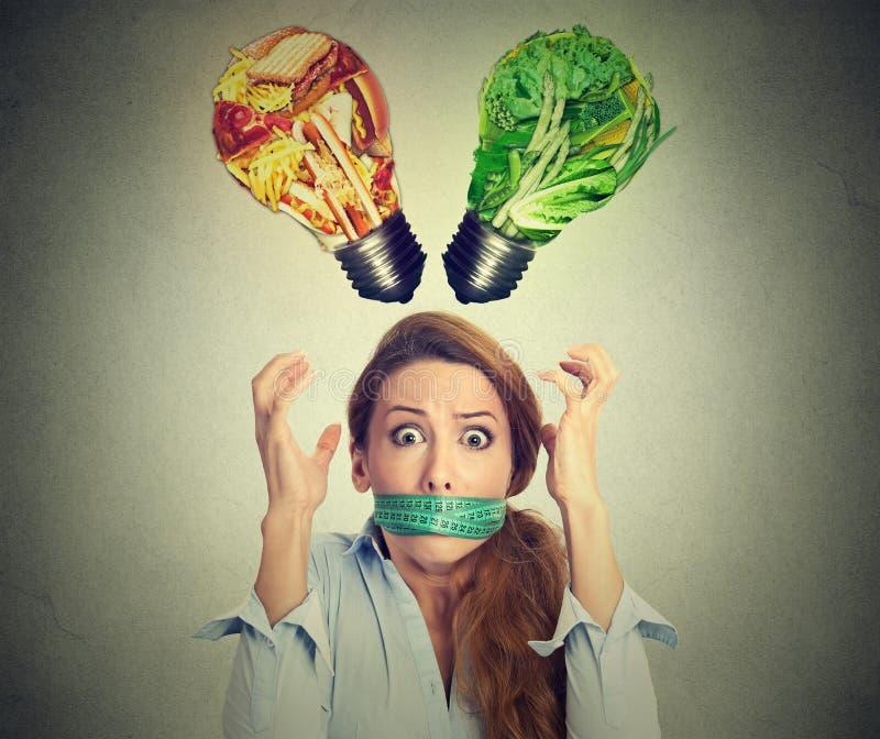 Concetto di sforzo di restrizione di dieta Donna frustrata con nastro adesivo di misurazione intorno alla bocca immagini stock libere da diritti