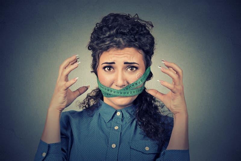 Concetto di sforzo di restrizione di dieta Donna frustrata con nastro adesivo di misurazione intorno alla bocca immagini stock