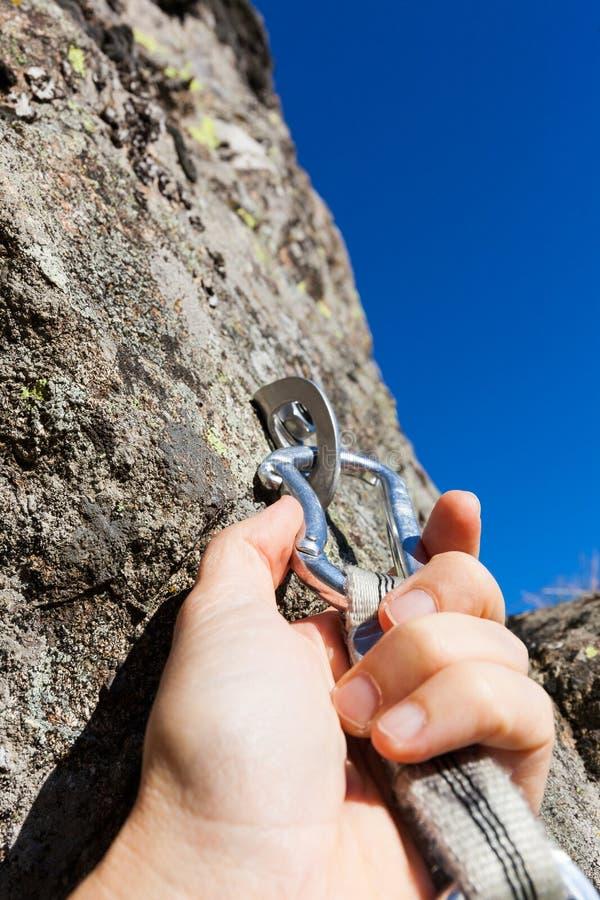 Concetto di sicurezza: lo scalatore inserisce un rapido-tiraggio in ancora su roccia immagini stock libere da diritti