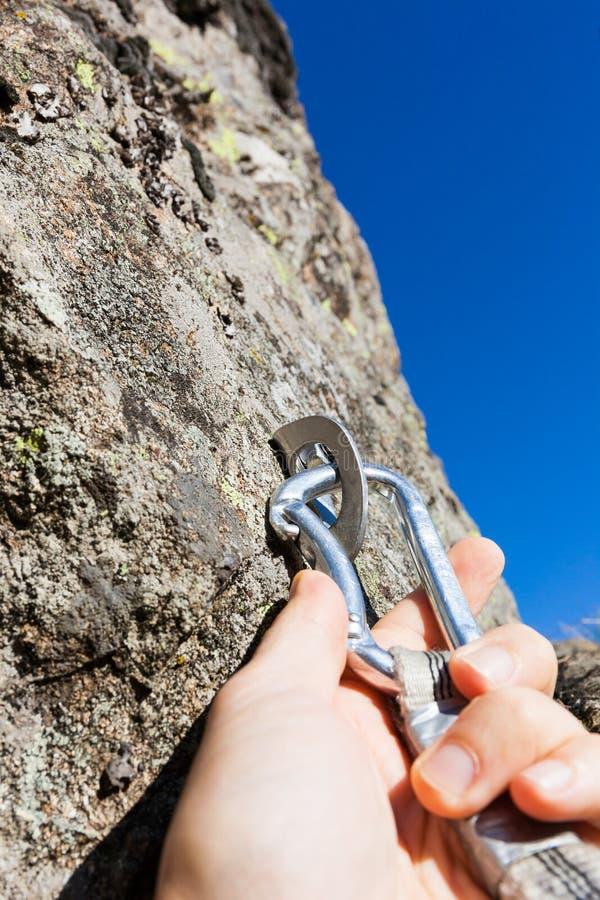 Concetto di sicurezza: lo scalatore inserisce un rapido-tiraggio in ancora su roccia immagine stock