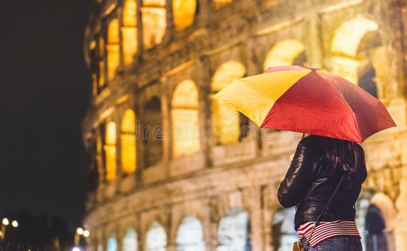 Concetto di smania dei viaggi Donna con un ombrello che esamina Colosseum fotografie stock libere da diritti