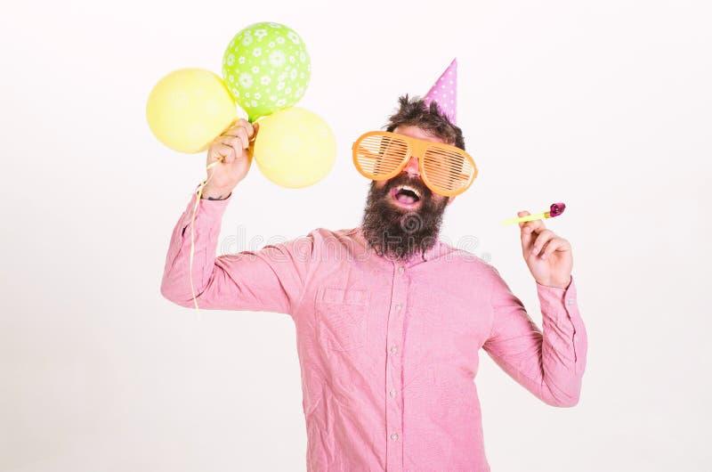 Concetto di sorpresa L'uomo con la barba ed i baffi sul fronte sorpreso tiene gli aerostati, fondo bianco Pantaloni a vita bassa  fotografie stock