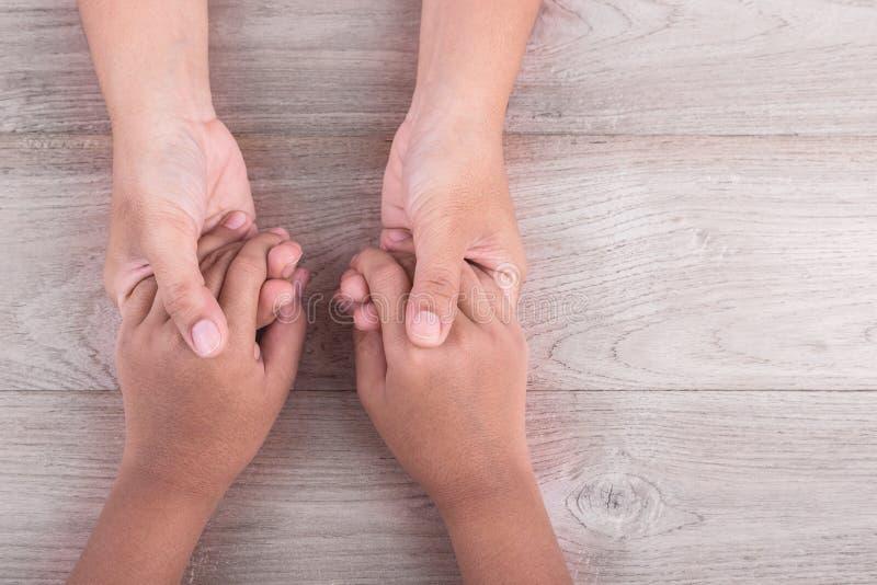 Concetto di sostegno e di aiuto: La donna tiene le sue mani dei ragazzini sulla b immagine stock libera da diritti