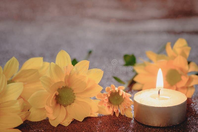 Concetto di speranza e di preghiera Retro luce della candela e fiore giallo con effetto della luce ed il fondo astratto di scinti immagini stock libere da diritti