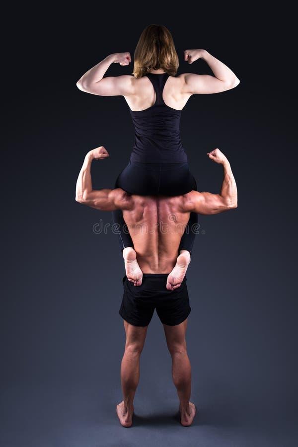Concetto di sport - donna sportiva che si siede sulle spalle del mA muscolare fotografia stock libera da diritti