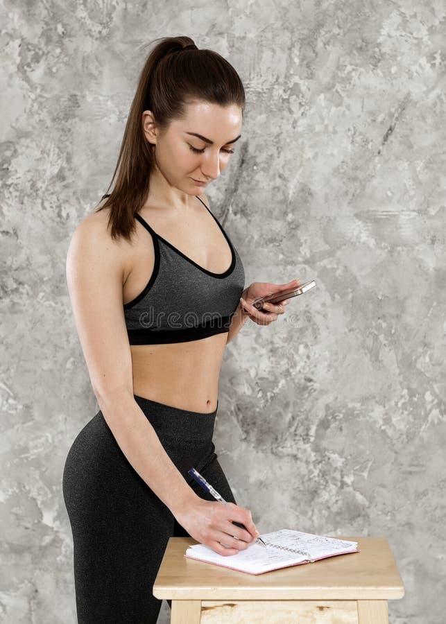 Concetto di sport, di forma fisica, di addestramento e di felicità - mani sportive della donna con le teste di legno rosso-chiaro fotografia stock