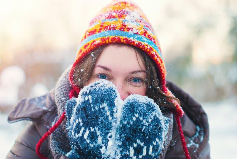 Concetto di stile di vita di inverno - giovane donna che gioca con la neve all'aperto immagini stock