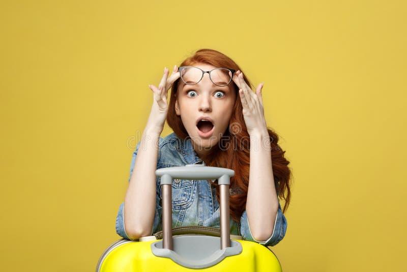 Concetto di stile di vita e di viaggio: Ritratto di una ragazza colpita in vestito dal denim con la valigia che esamina macchina  fotografia stock