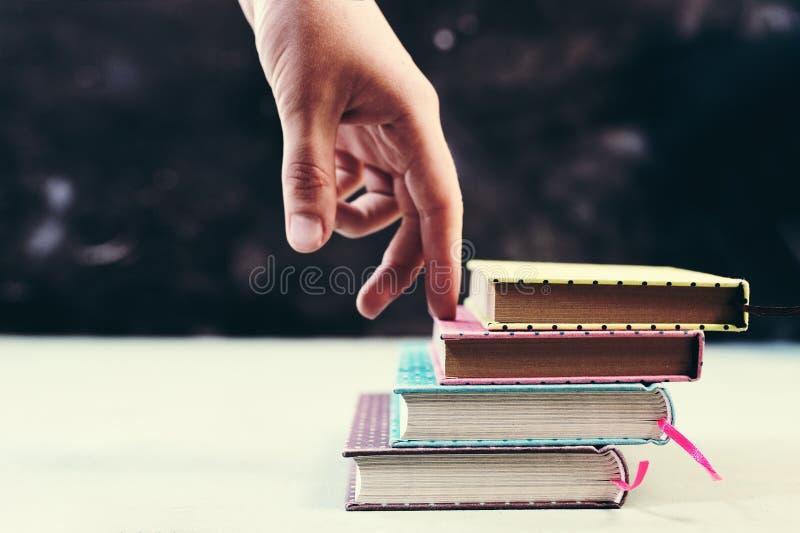 Concetto di successo con le dita che scalano le scale fatte della pila di libri immagine stock