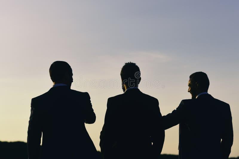 Concetto di successo e di affari Siluette degli uomini che stanno contro il tramonto I capi discutono il progetto immagini stock libere da diritti