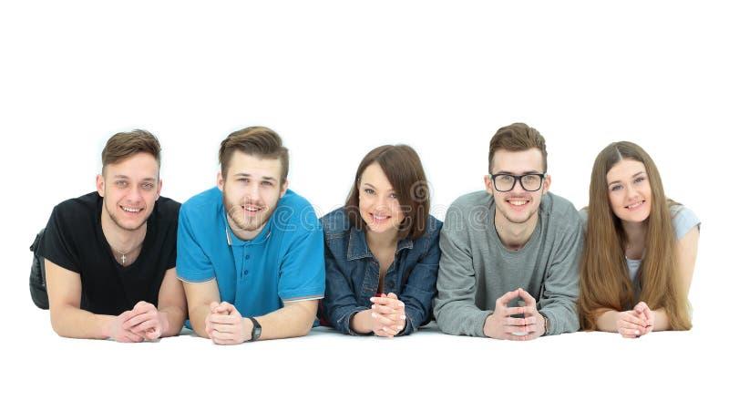 Concetto di successo - gruppo felice dello studente che si trova su un gabinetto bianco del manifesto fotografia stock