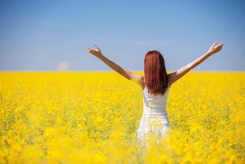Concetto di successo di libertà della gente Donna felice nel campo con i fiori al giorno soleggiato nella campagna Fondo di belle fotografie stock libere da diritti