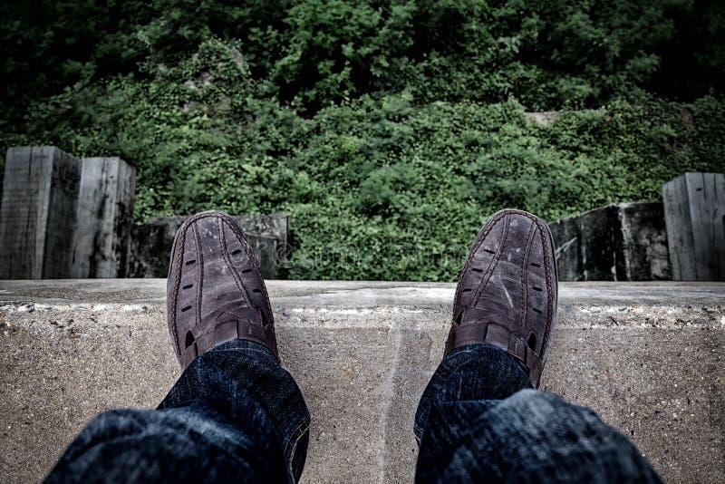 Concetto di suicidio , Giovane depresso che esamina giù il suo scarpa a fotografie stock