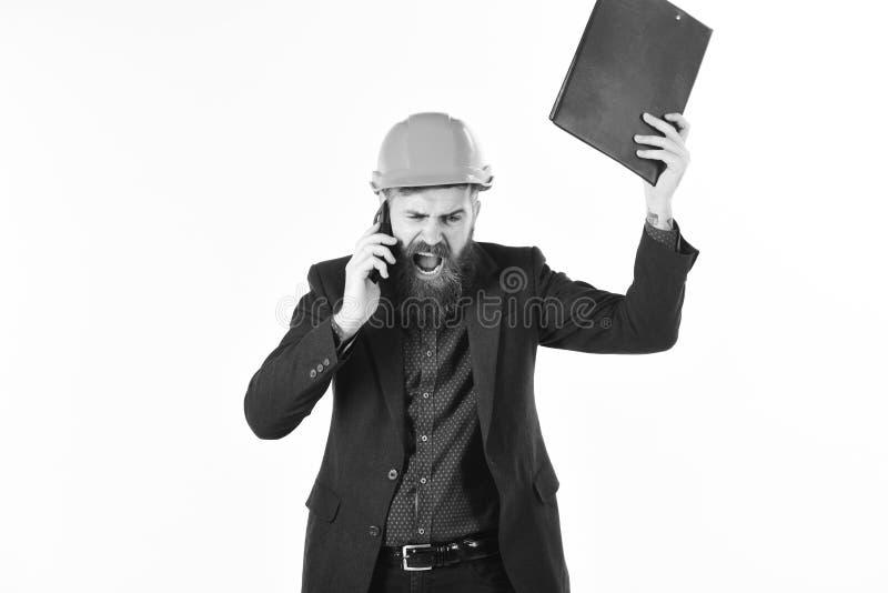Concetto di sviluppo e di ingegneria L'architetto o l'ingegnere arrabbiato grida e tiene il telefono cellulare Ingegneria civile fotografia stock libera da diritti