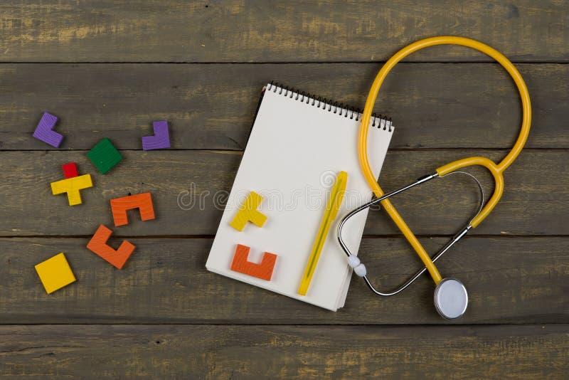 Concetto di sviluppo per bambini e#x27;è sano - blocco appunti vuoto, stethoscopio giallo, puzzle colorati in legno fotografia stock