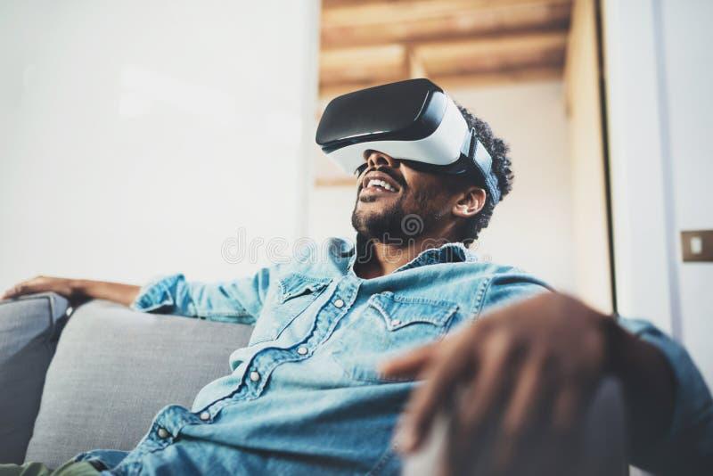 Concetto di tecnologia, di gioco, di spettacolo e della gente Uomo africano barbuto che gode della cuffia avricolare di vetro di  fotografia stock