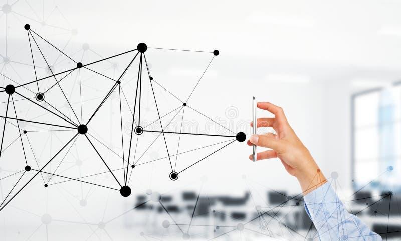 Concetto di tecnologia e di affari con la griglia della rete ed uomo che per mezzo del dispositivo fotografie stock