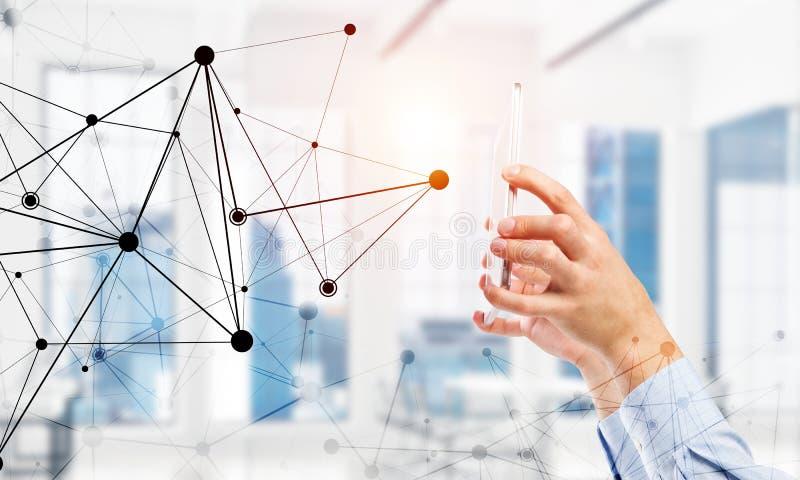Concetto di tecnologia e di affari con la griglia della rete ed uomo che per mezzo del dispositivo immagine stock