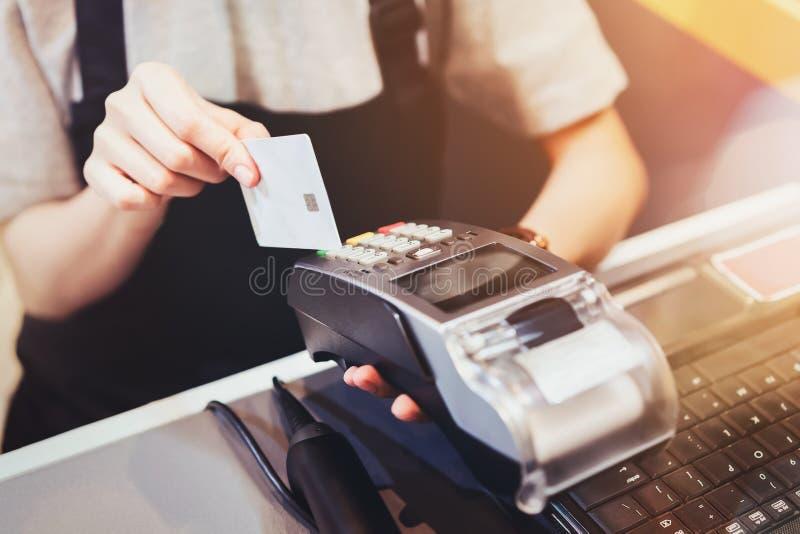 Concetto di tecnologia nell'acquisto senza usando contanti Fine su della carta di credito di uso della mano che swiping macchina  fotografia stock
