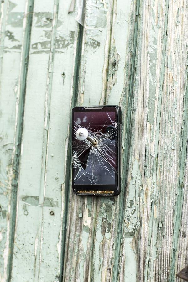 Concetto di tecnologia obsoleta: il telefono cellulare ha inchiodato al recinto un grande chiodo immagini stock