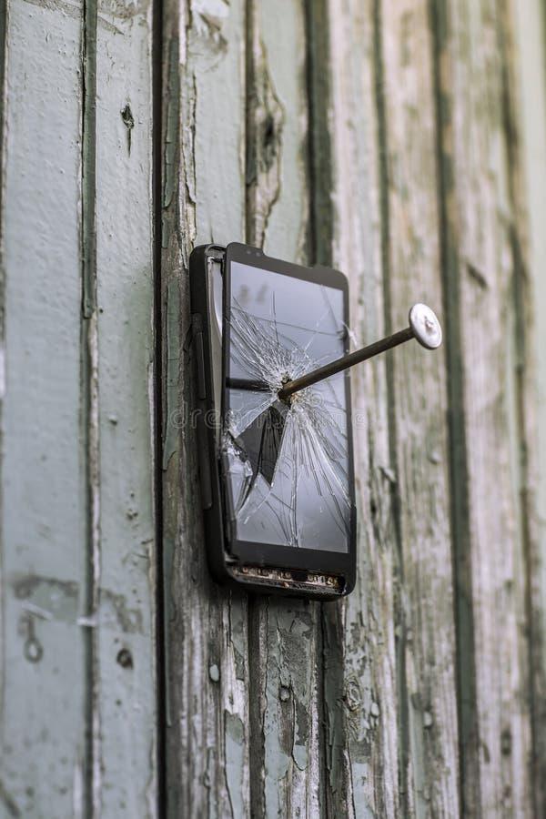 Concetto di tecnologia obsoleta: il telefono cellulare ha inchiodato al recinto un grande chiodo immagine stock libera da diritti