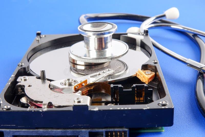CONCETTO DI TECNOLOGIA DI RIPARAZIONE E DI RECUPERO: Drive del hard disk HDD con lo stetoscopio isolato su un fondo blu immagine stock libera da diritti