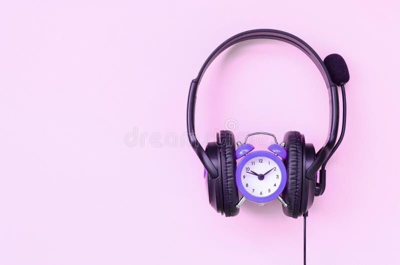 Concetto di tempo a musica d'ascolto Sveglia e cuffie fotografia stock