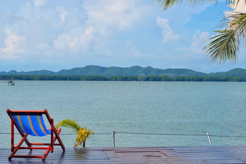 Concetto di tempo di vacanza, tempo della spiaggia sulla terra di legno con la vista del mare immagini stock libere da diritti