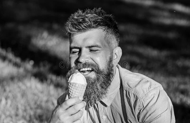 Concetto di tentazione Uomo barbuto con il cono gelato L'uomo con la barba ed i baffi sul fronte felice godono del gelato, erba s immagine stock