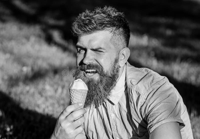 Concetto di tentazione Uomo barbuto con il cono gelato L'uomo con la barba lunga mangia il gelato, mentre si siede su erba Uomo c immagine stock libera da diritti