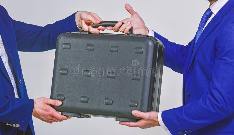 Concetto di trasferimento di affari Cartella maschio della tenuta della mano Consegna del caso in mani dei soci commerciali Conse fotografie stock