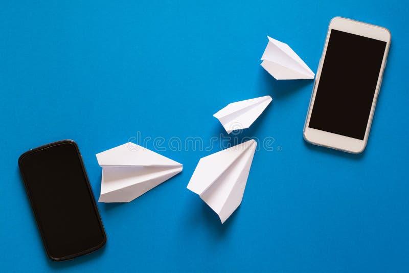 Concetto di trasferimento di dati Trasmissione del messaggio Due smartphones mobili ed aeroplani di carta fotografia stock