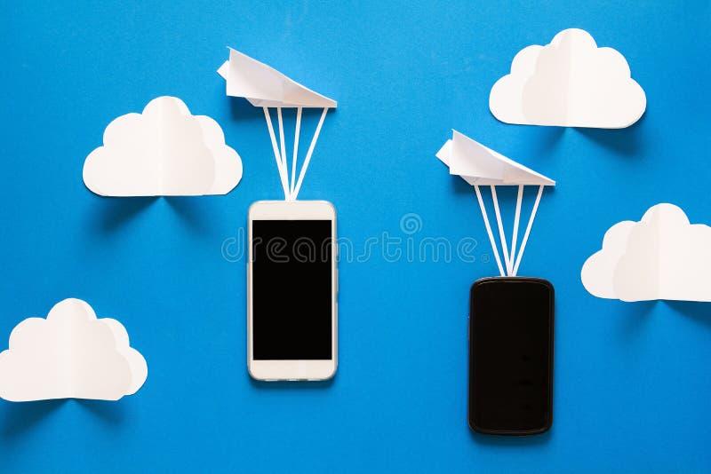 Concetto di trasferimento di dati Trasmissione del messaggio Due smartphones mobili ed aeroplani di carta fotografie stock
