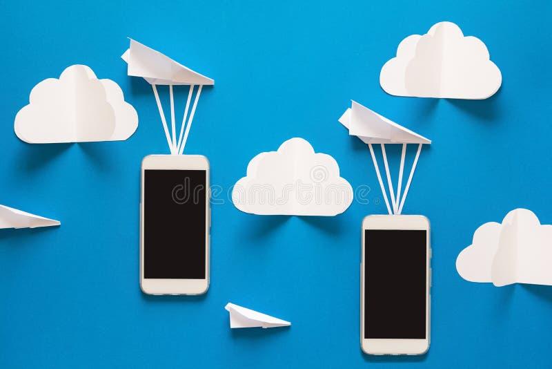 Concetto di trasferimento di dati Trasmissione del messaggio Due smartphones mobili ed aeroplani di carta immagini stock