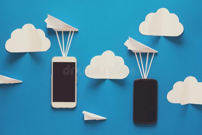 Concetto di trasferimento di dati Trasmissione del messaggio Due smartphones mobili ed aeroplani di carta su fondo blu origami immagini stock libere da diritti