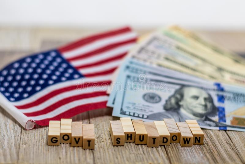 Concetto di U.S.A. di arresto di governo con le fatture di soldi e della bandiera americana su fondo bianco e sul bordo di legno immagini stock libere da diritti