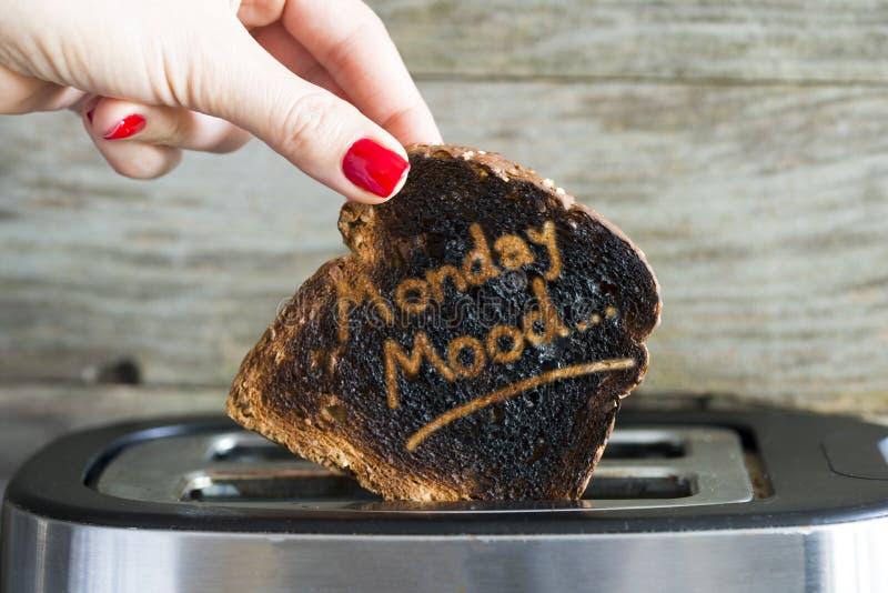 Concetto di umore di lunedì con la fetta di pane bruciato del pane tostato in mano della donna immagini stock libere da diritti