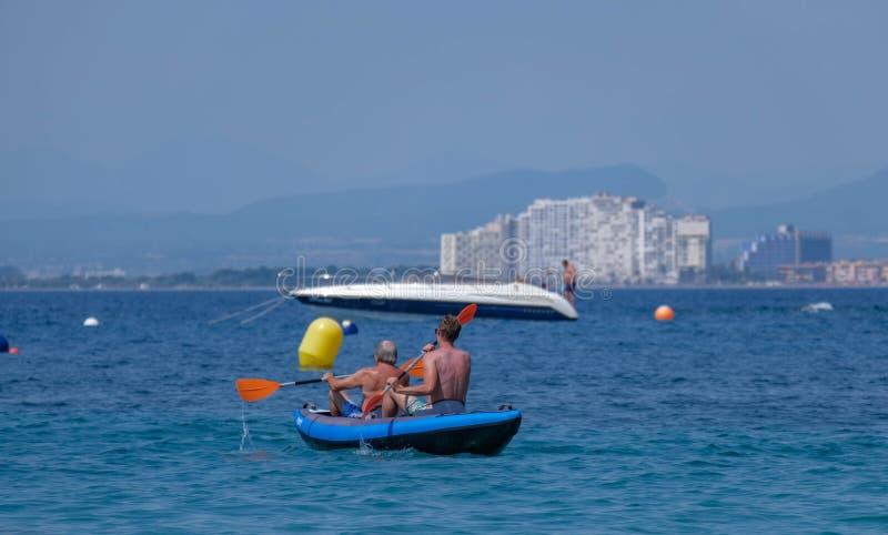Concetto di vacanza della spiaggia di estate, due uomini che remano una barca fotografie stock