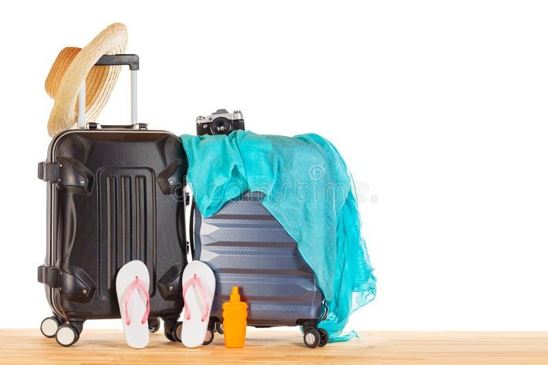 Concetto di vacanze estive Bagaglio delle valigie con il cappello di paglia, il pareo blu, i Flip-flop, la bottiglia della lozion fotografia stock libera da diritti