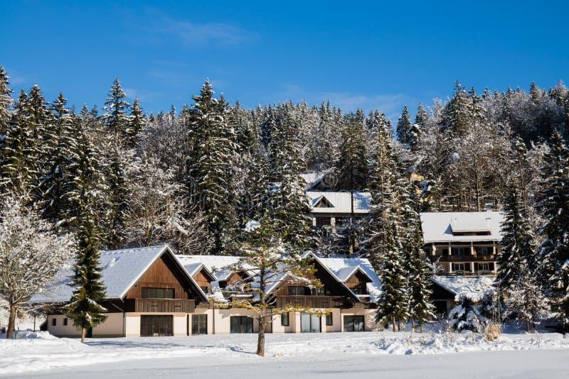 Concetto di vacanze invernali di spesa in casa di legno idilliaca in precipitazioni nevose accanto al lago, Kranjska Gora, Sloven fotografia stock