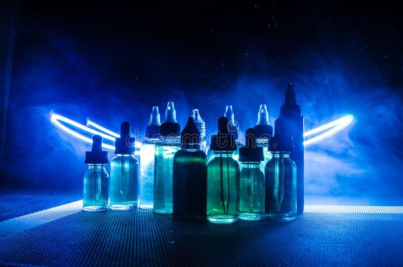 Concetto di Vape Nuvole di fumo e bottiglie liquide del vape su fondo scuro Effetti della luce immagini stock