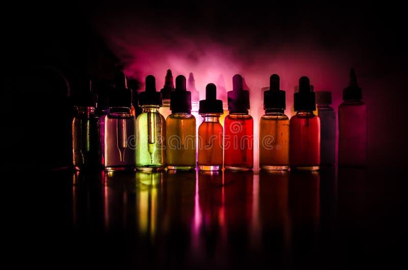 Concetto di Vape Nuvole di fumo e bottiglie liquide del vape su fondo scuro Effetti della luce Utile come pubblicità o del vape o fotografie stock libere da diritti