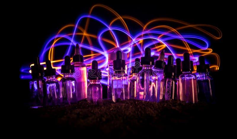 Concetto di Vape Nuvole di fumo e bottiglie liquide del vape su fondo scuro Effetti della luce Utile come pubblicità o del vape o fotografia stock