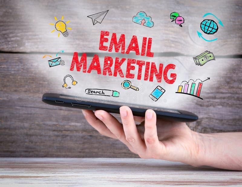 Concetto di vendita del email computer della compressa nella mano Vecchia priorità bassa di legno immagini stock