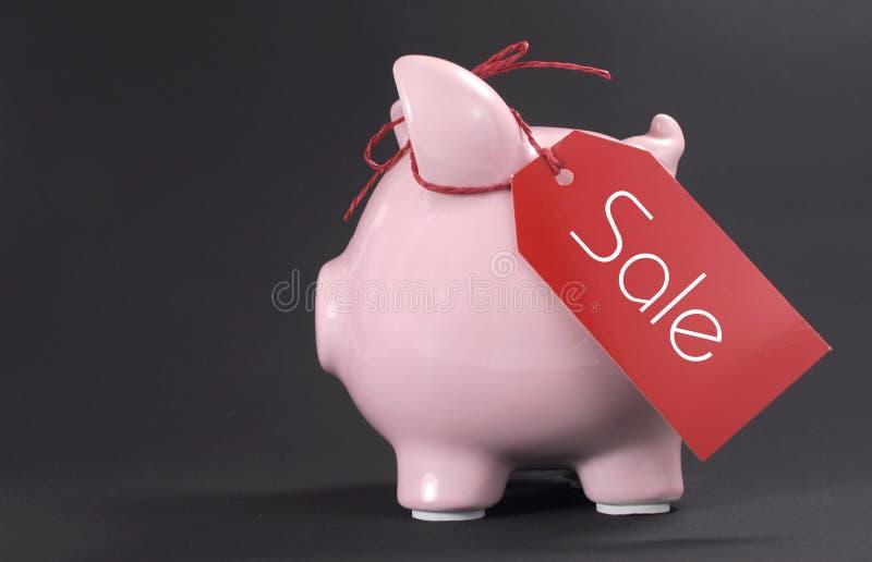 Concetto di vendita di acquisto di Black Friday con l'etichetta rossa di vendita dei biglietti che pende dal porcellino salvadana fotografia stock