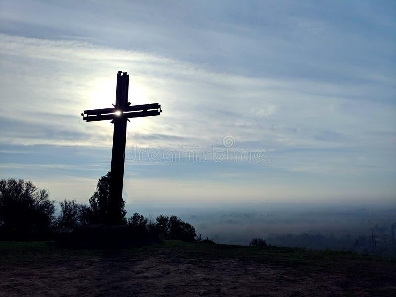 Concetto di venerdì santo: Incrocio della siluetta di Jesus Christ sul cielo di alba del prato fotografie stock libere da diritti