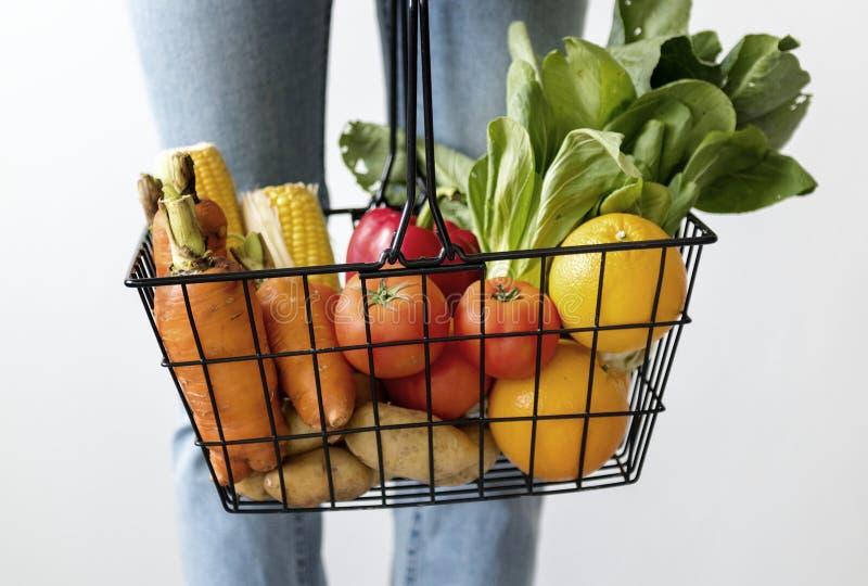 Concetto di verdure di acquisto del canestro della tenuta della donna immagini stock libere da diritti