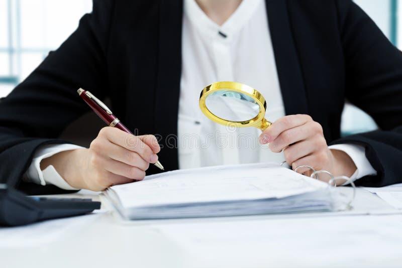 Concetto di verifica interna - donna con l'ispezione della lente d'ingrandimento immagine stock