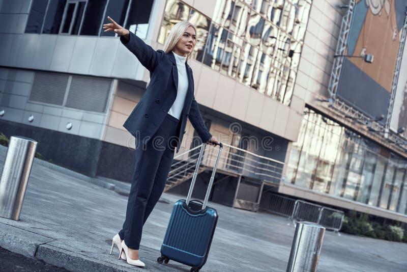 Concetto di viaggio di affari e di viaggio Giovane donna sorridente con il taxi di cattura della borsa di viaggio immagine stock libera da diritti